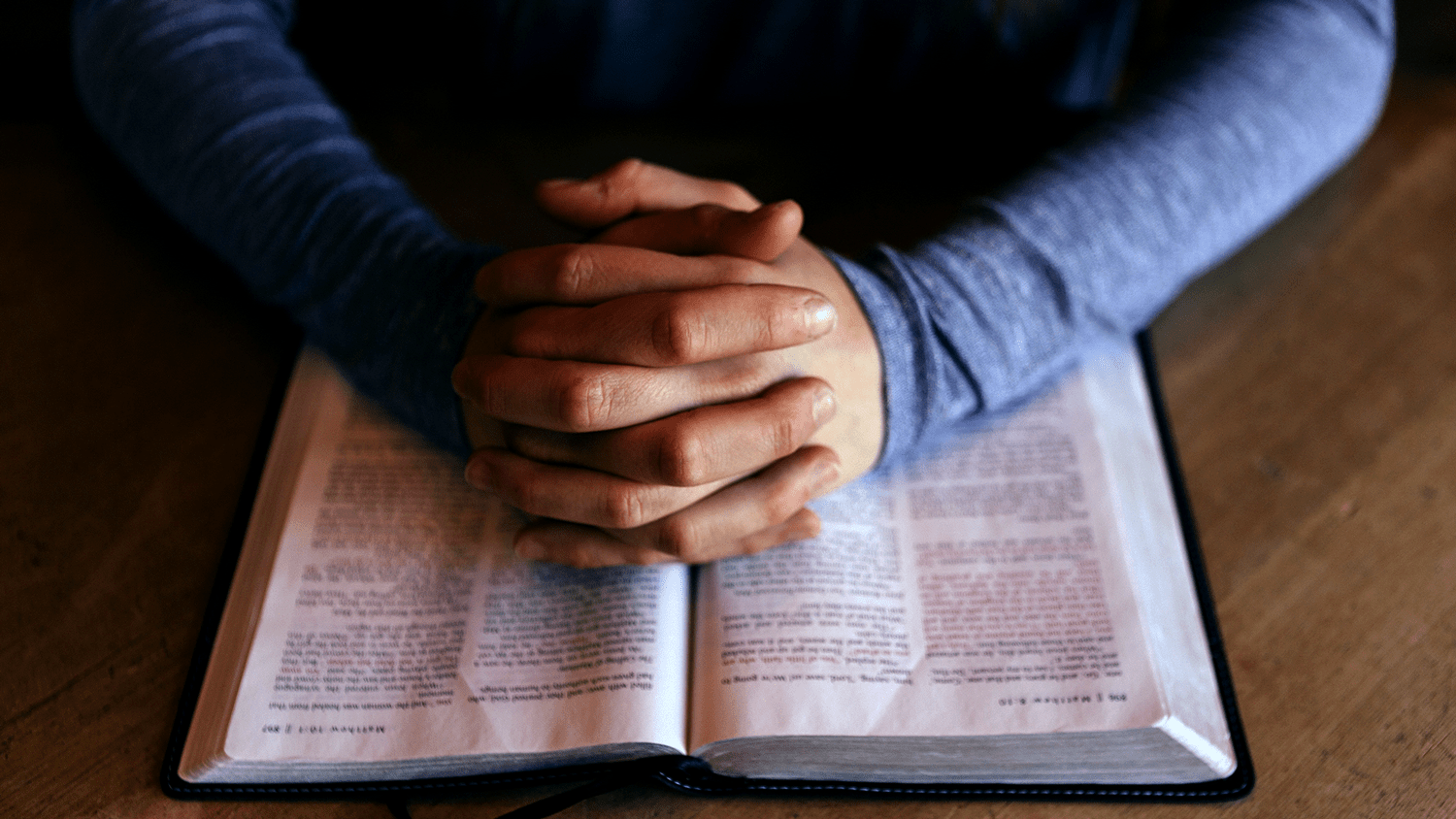 An image of someone at prayer with an open Bible.
