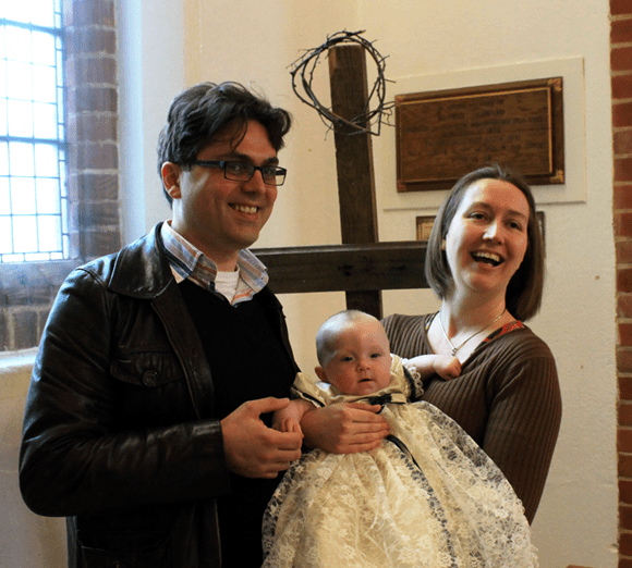 An image of two people holding a baby in St. Peter's Church, Buntingford.